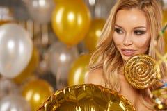 Retrato de la mujer joven rubia entre los globos y la cinta de oro Fotografía de archivo libre de regalías