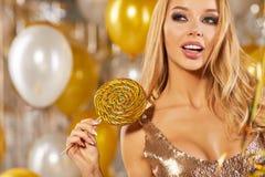 Retrato de la mujer joven rubia entre los globos y la cinta de oro Imagenes de archivo