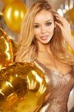 Retrato de la mujer joven rubia entre los globos y la cinta de oro Fotos de archivo