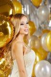 Retrato de la mujer joven rubia entre los globos y la cinta de oro Fotos de archivo libres de regalías