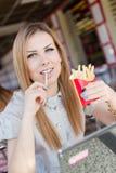 Retrato de la mujer joven rubia hermosa que come las patatas fritas en el restaurante que mira la cámara Fotografía de archivo libre de regalías