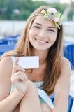 Retrato de la mujer joven rubia hermosa que tiene tarjeta de visita en blanco sonriente de la diversión y que se considera feliz  Fotos de archivo libres de regalías