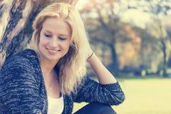Retrato de la mujer joven rubia sonriente que mira fijamente abajo en el lado Imagenes de archivo