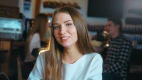 Retrato de la mujer joven sonriente atractiva en restaurante metrajes