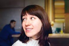 Retrato de la mujer joven sonriente con el pelo oscuro que se sienta en una cafetería Foto de archivo