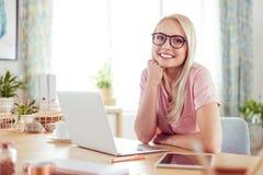 Retrato de la mujer joven sonriente en el escritorio en casa imágenes de archivo libres de regalías