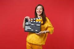 Retrato de la mujer joven sonriente en el suéter amarillo de la piel que sostiene clapperboard negro clásico del rodaje de pelícu imagenes de archivo