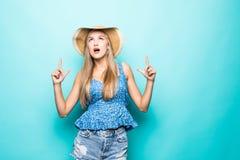 Retrato de la mujer joven sonriente en sombrero del verano de la paja que señala los dedos índices para arriba en el espacio de l fotos de archivo libres de regalías
