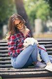 Retrato de la mujer joven sonriente feliz atractiva que sostiene el pequeño perro lindo imagenes de archivo
