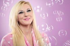 Retrato de la mujer joven sonriente que juega con las burbujas en el CCB rosado Imagenes de archivo
