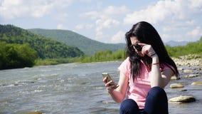 Retrato de la mujer joven sorprendida del encanto con los vidrios y smartphone redondos Fondo del río de la montaña cárpata foto de archivo