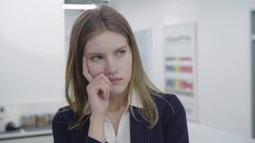 Retrato de la mujer joven triste en cuesti?n en la ropa formal que mira lejos y en la c?mara, pensando en su cierre del problema almacen de video