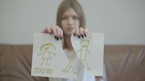 Retrato de la mujer joven triste que destroza el dibujo de los niños con la imagen de la mamá y del papá Problemas en la relaci?n metrajes