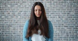 Retrato de la mujer joven triste que mira alrededor entonces la cámara en fondo del ladrillo metrajes