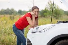 Retrato de la mujer joven triste que se coloca en el coche quebrado en mecánico que espera del camino del campo para Fotos de archivo
