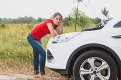 Retrato de la mujer joven triste que se inclina en el motor del coche quebrado en campo Foto de archivo