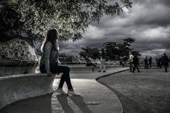 Retrato de la mujer joven y atractiva, que se está sentando en el banco Imagen de archivo