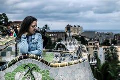 Retrato de la mujer joven y atractiva, que se está sentando en el banco en el parque Guell Foto de archivo libre de regalías
