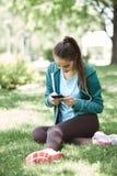 Retrato de la mujer joven y deportiva en la ropa de deportes que se sienta con el smartphone en la hierba en parque Fotos de archivo