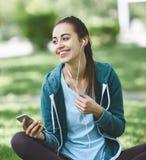 Retrato de la mujer joven y deportiva en la ropa de deportes que se sienta con el smartphone en la hierba en parque Foto de archivo