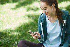 Retrato de la mujer joven y deportiva en la ropa de deportes que se sienta con el smartphone en la hierba en parque Imagen de archivo libre de regalías