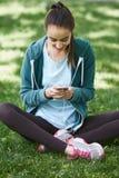 Retrato de la mujer joven y deportiva en la ropa de deportes que se sienta con el smartphone en la hierba en parque Fotografía de archivo libre de regalías