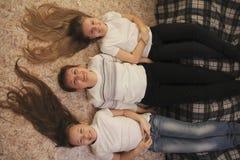 Retrato de la mujer joven y dos de los adolescentes femeninos que mienten en el piso en casa, sus pies en el sofá Imágenes de archivo libres de regalías