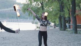 Retrato de la mujer linda joven en la máscara que realiza una demostración con la llama delante de árboles Demostración experta d almacen de metraje de vídeo