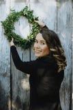 Retrato de la mujer linda que cuelga una guirnalda de la Navidad en su hogar Fotos de archivo