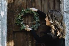 Retrato de la mujer linda que cuelga una guirnalda de la Navidad en su hogar Foto de archivo