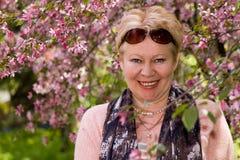 Retrato de la mujer madura cerca de un manzano decorativo Foto de archivo libre de regalías