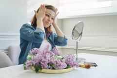Retrato de la mujer madura con el espejo del maquillaje que da masajes a su cara y cuello, 40 a?os femeninos hermosos fotografía de archivo