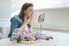 Retrato de la mujer madura con el espejo del maquillaje que da masajes a su cara y cuello, 40 a?os femeninos hermosos fotos de archivo libres de regalías