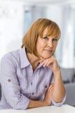 Retrato de la mujer madura con la mano en la barbilla que se sienta en la tabla en casa foto de archivo