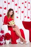 Retrato de la mujer magnífica en el vestido rojo que se sienta en el sofá con flo Fotografía de archivo libre de regalías