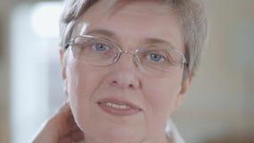 Retrato de la mujer mayor atractiva con los vidrios que miran in camera de fijación de su pelo con sonrisa agradable dentro cerca almacen de metraje de vídeo