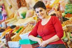 Retrato de la mujer mayor cerca de la especia, de las nueces y de la otra comida en mercado oriental Imagen de archivo