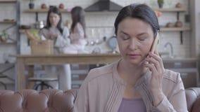 Retrato de la mujer mayor con el pelo negro coloreado que habla por el teléfono celular que se sienta en el sofá de cuero almacen de metraje de vídeo