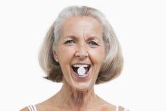 Retrato de la mujer mayor con la píldora entre sus dientes contra el fondo blanco Imagen de archivo