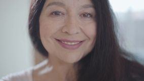 Retrato de la mujer mayor coqueta atractiva con el pelo oscuro largo magnífico y la sonrisa amplia agradable que fijan su ceja y metrajes