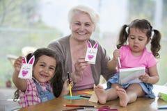 Retrato de la mujer mayor feliz que muestra el conejo del arte mientras que se sienta con las nietas en casa Foto de archivo libre de regalías