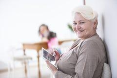 Retrato de la mujer mayor feliz que usa la tableta digital con la aguja en casa Fotografía de archivo libre de regalías