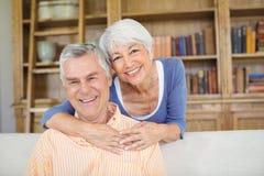 Retrato de la mujer mayor que abraza a un hombre en sala de estar Imagen de archivo