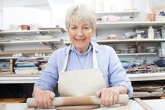 Retrato de la mujer mayor que desarrolla a Clay In Pottery Studio Imagen de archivo libre de regalías