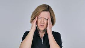 Retrato de la mujer mayor que gesticula el dolor de cabeza, tensión almacen de metraje de vídeo