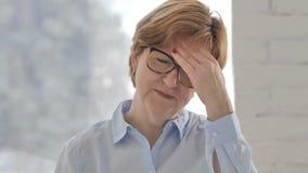 Retrato de la mujer mayor que gesticula el dolor de cabeza, tensión metrajes