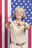 Retrato de la mujer mayor que señala en la insignia de la elección contra bandera americana Fotos de archivo libres de regalías