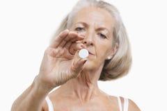 Retrato de la mujer mayor que sostiene una píldora contra el fondo blanco Foto de archivo