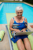 Retrato de la mujer mayor que usa el ordenador portátil en sillón Imágenes de archivo libres de regalías