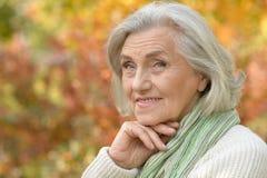 Retrato de la mujer mayor sonriente agradable que presenta en fondo otoñal borroso fotografía de archivo